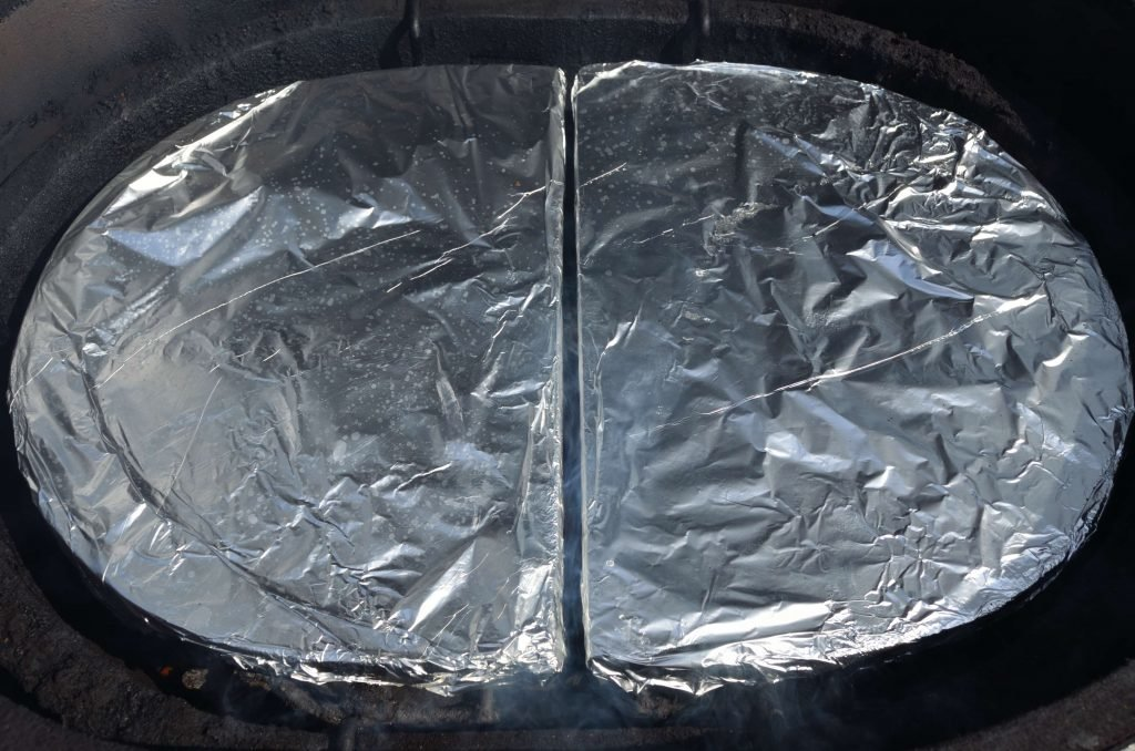 Position the drip pan racks and ceramic d plates over the coals and wood. We highly recommend covering the d plates in foil for easy cleaning. Also, be conscious of their position to make sure there is an even gap around in the center.