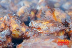 A honey butter glazed lot of chicken wings on a smoker