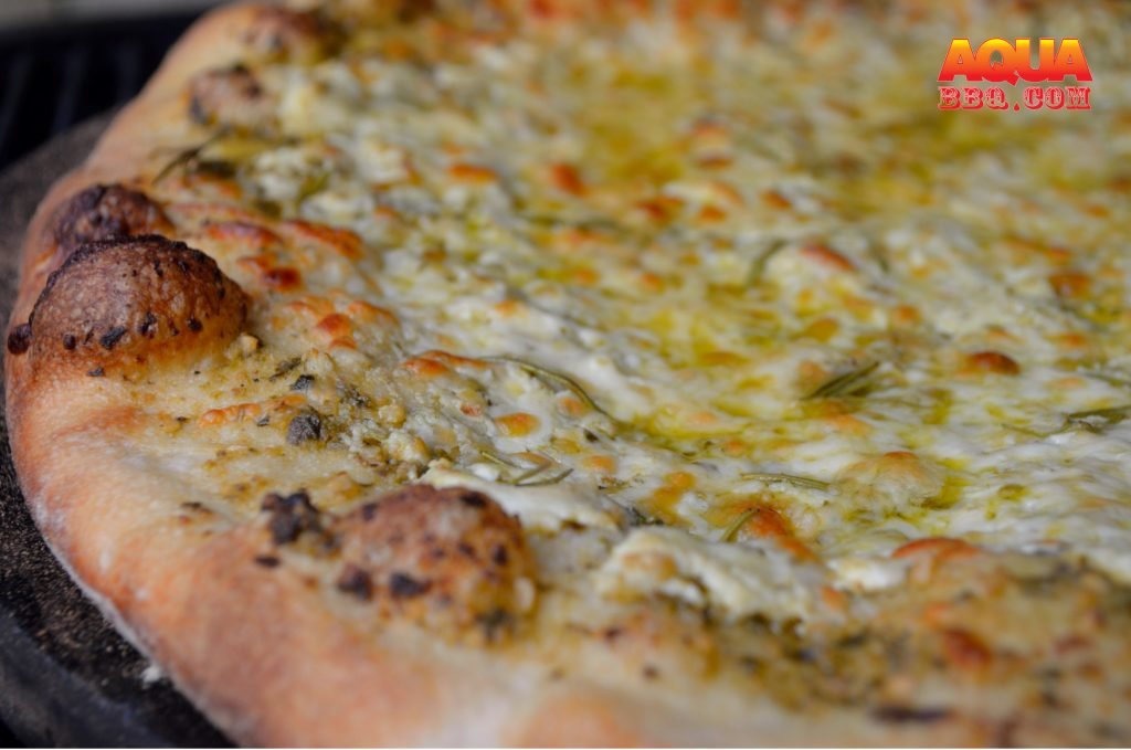 White Pizza on the Primo with ricotta, pesto, rosemary, and mozzarella.