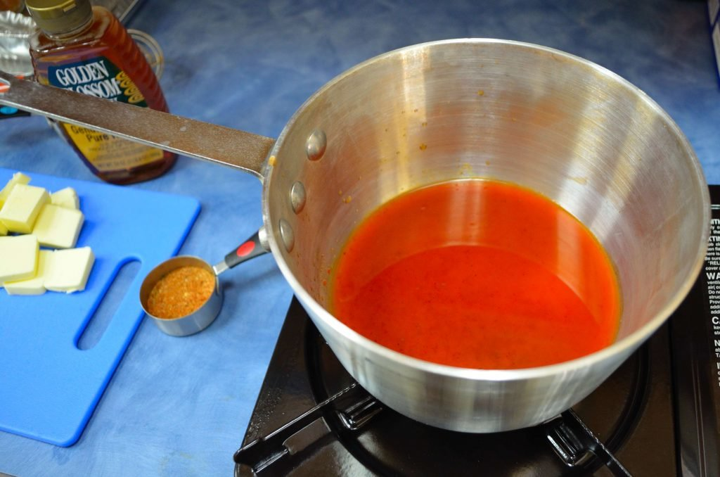 Heat the hot sauce until it just begins to boil then reduce heat to low.