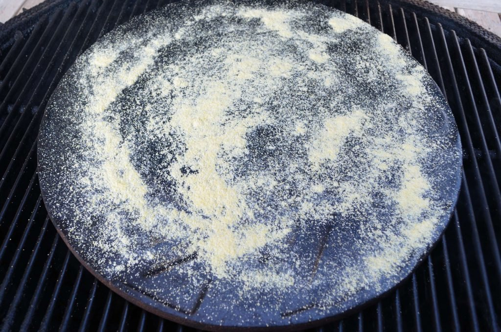 Give your pizza stone a healthy sprinkle of cornmeal right before you put on the pizza.