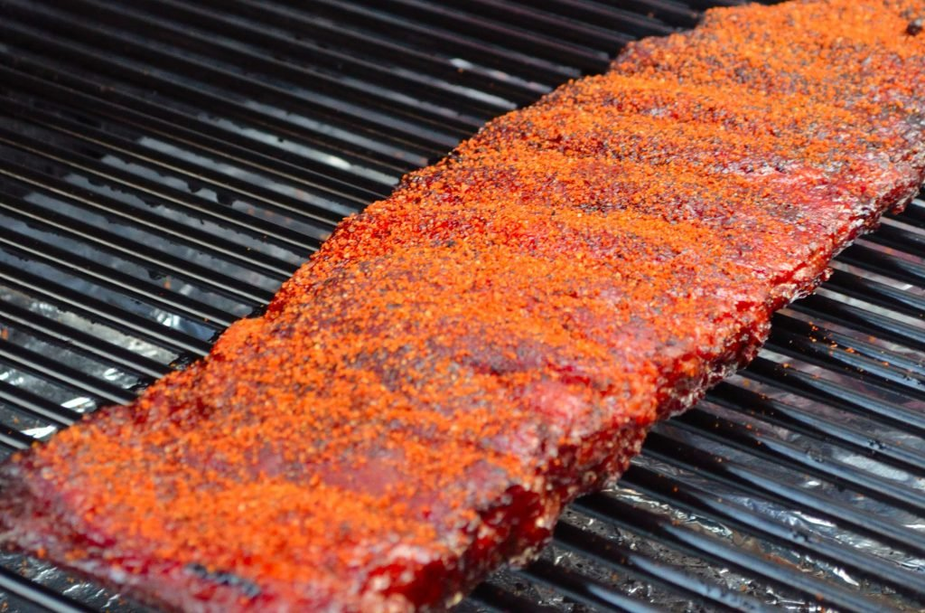 At this point you can keep the ribs wrapped in foil and towel in a cooler until you are ready to serve. (They will stay hot for hours!)  When you are ready to serve, put them back on the Primo and give them another healthy sprinkle of rub.