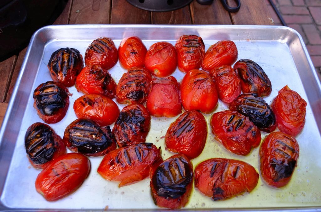 We halved the plum tomatoes before cooking. Return the tomoatoes to sheet pans when done to help collect and juices. The skins will simply pull off and then we removed any white core parts from the middle. Remove the seeds over a chinois on top of the sheet pan to collect juices. Process the tomatoe meat in batches in a food processor.