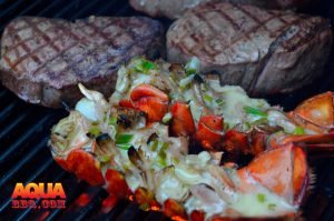 Upside down Lobster tails and steaks being grilled