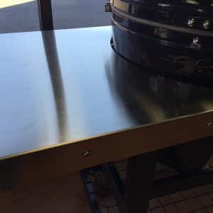 Stainless steel side shelves on a Primo Grill