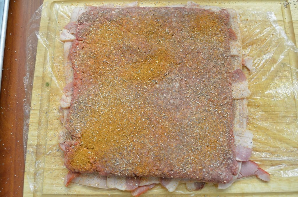 Next, stuff a plastic freezer bag with about 2lbs of ground chuck and evenly flatten the bag. Tear open the bag and lay the beef on the bacon. Season with your favorite BBQ rub - here with used a combination of SuckleBusters SPG and Competition Rubs.